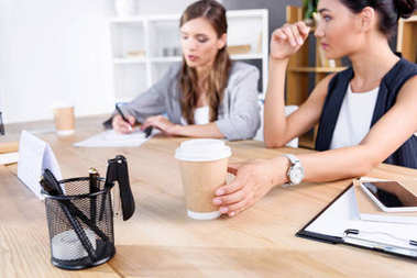 Businesswomen with coffee at workplace