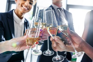 Cropped shot of young business colleagues drinking champagne in office stock vector