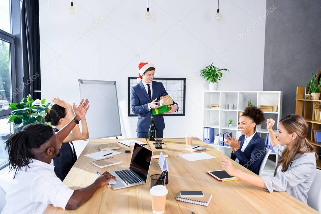 businessman presenting gifts to colleagues