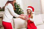 madre che presenta il regalo di Natale per la figlia
