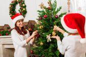 Matka a dcera zdobí vánoční stromeček