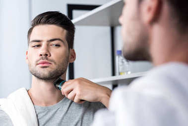 Man shaving with electric trimmer
