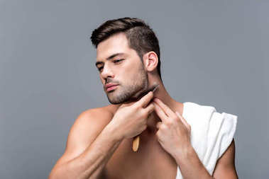 man shaving with straight razor