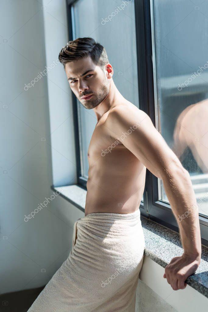 shirtless man leaning back on windowsill
