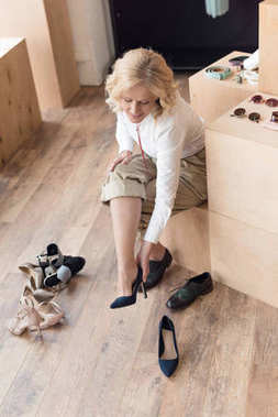 woman trying on shoes in clothing store