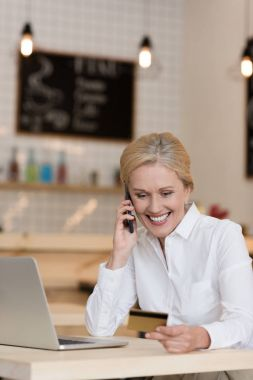 businesswoman with credit card talking on smartphone