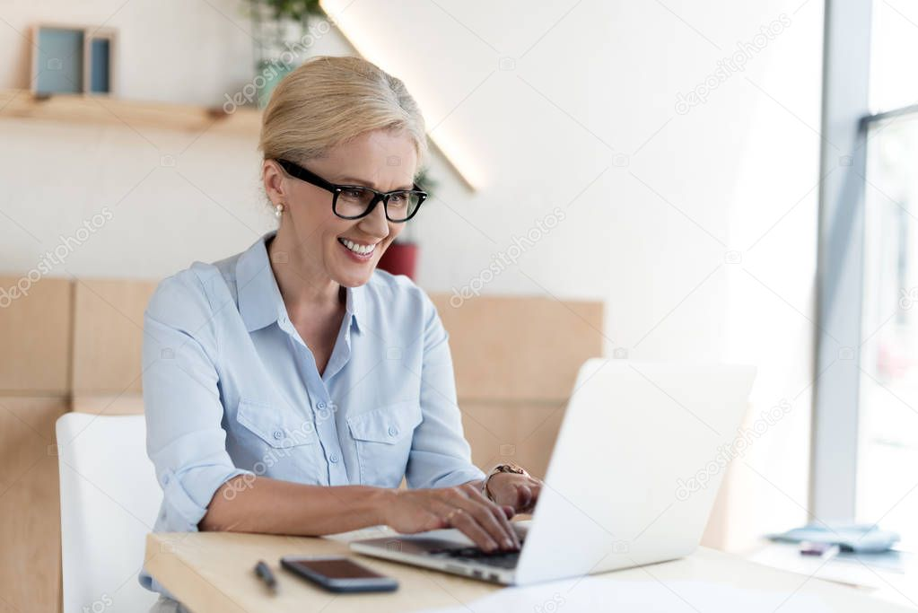 Smiling mature businesswoman in eyeglasses using laptop in cafe