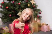 Fotografie Kind mit Daumen oben am Weihnachtsbaum