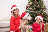 Familie mit Hund in Weihnachtsmützen