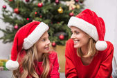 Fotografie mother and daughter in Santa hats on christmas