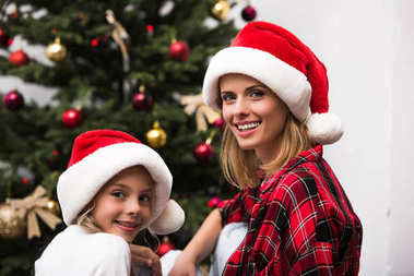 Beautiful happy mother and daughter in santa hats smiling at camera stock vector