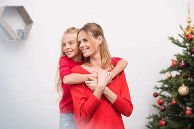 mother and daughter hugging at christmas tree