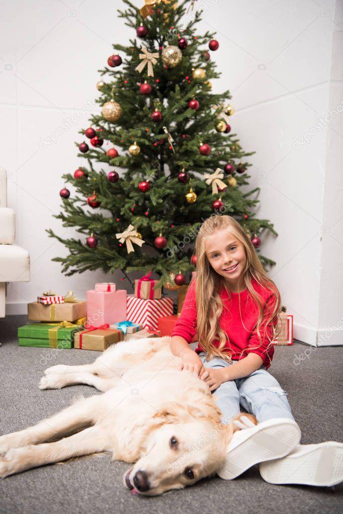 kid with dog at christmas tree