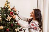 žena zdobení vánoční strom