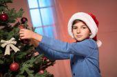Junge schmücken Weihnachtsbaum