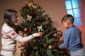 Fotografie Mutter und Sohn schmücken Weihnachtsbaum