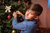 Fotografie Junge schmücken Weihnachtsbaum