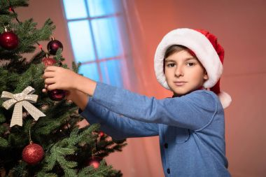 Cute little boy in santa hat decorating christmas tree and looking at camera stock vector