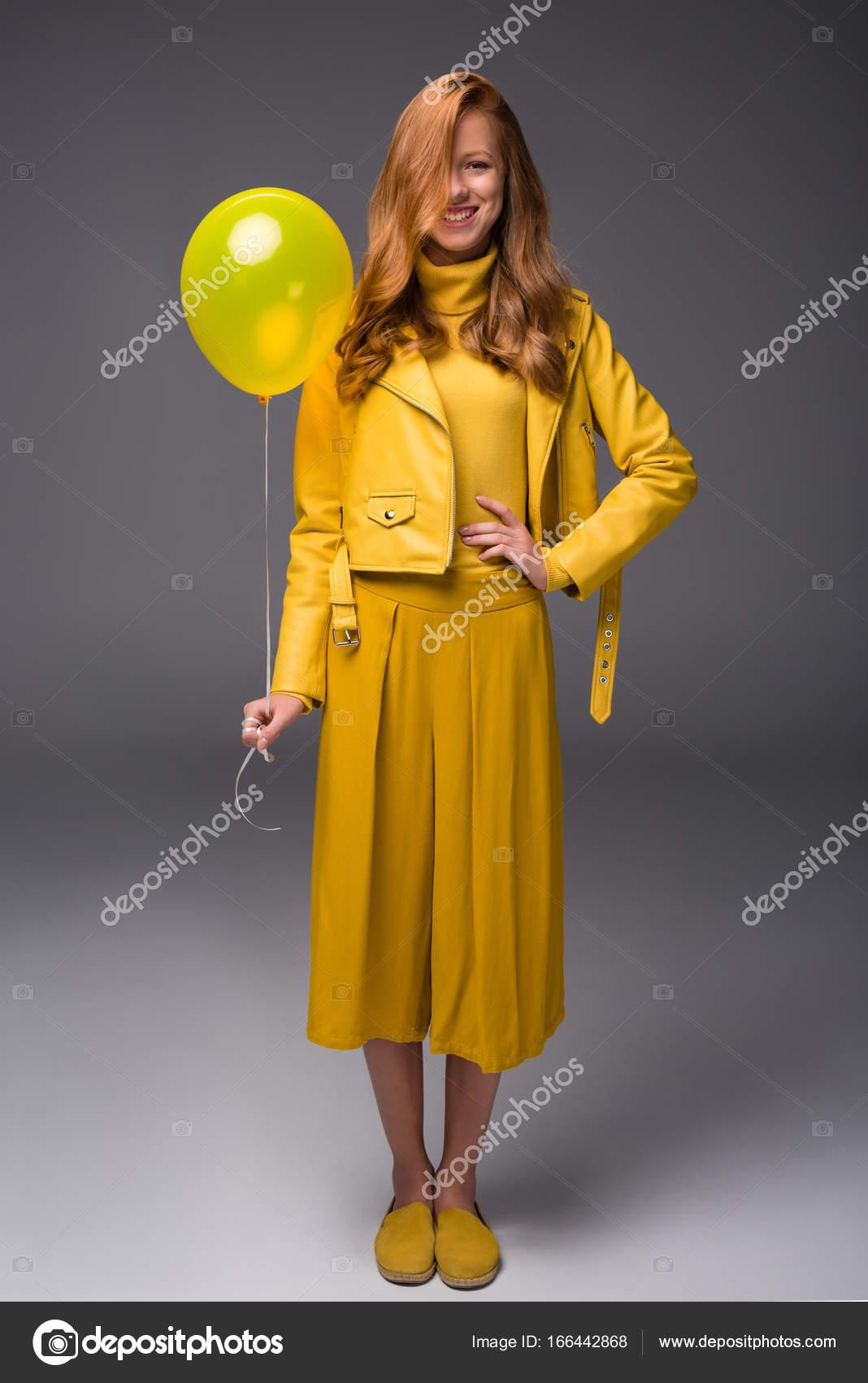 54cfcdd94b8 Ragazza alla moda attraente di redhead in vestiti di gialli con il pallone