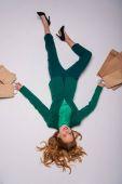 Fotografia ragazza sdraiata con borse della spesa