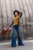 elegantní dívka v klobouku s kufrem