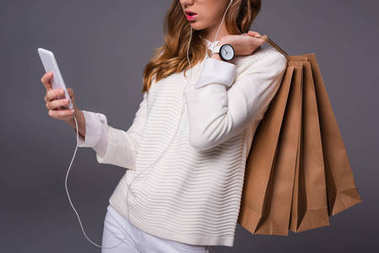 Girl with smartphone and shopping bags