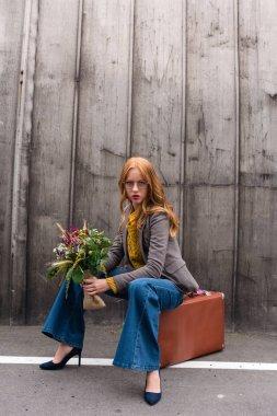 girl sitting on vintage suitcase