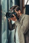 fotograf s kamerou na okno