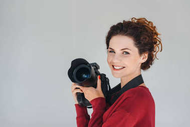 Professional female photographer with digital photo camera in photo studio, isolated on grey stock vector