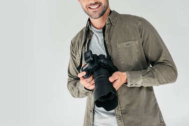 Cropped view of professional male photographer with digital photo camera in photo studio, isolated on grey stock vector