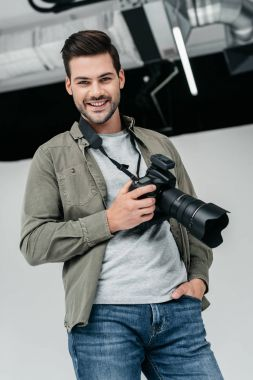 Professional male photographer with digital photo camera in photo studio stock vector
