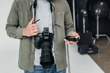 Cropped view of professional male photographer with digital photo camera and light meter in photo studio stock vector