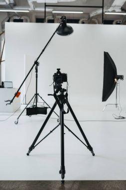 camera in photo studio with lighting equipment