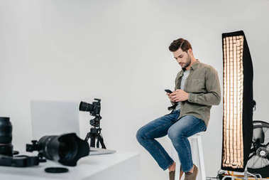 Professional male photographer with smartphone and digital photo camera on tripod in photo studio stock vector