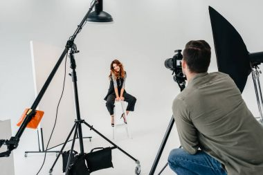 Professional photographer and beautiful model on fashion shoot in photo studio with lighting equipment stock vector