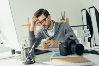 Tired male photographer working with graphics tablet in modern office stock vector