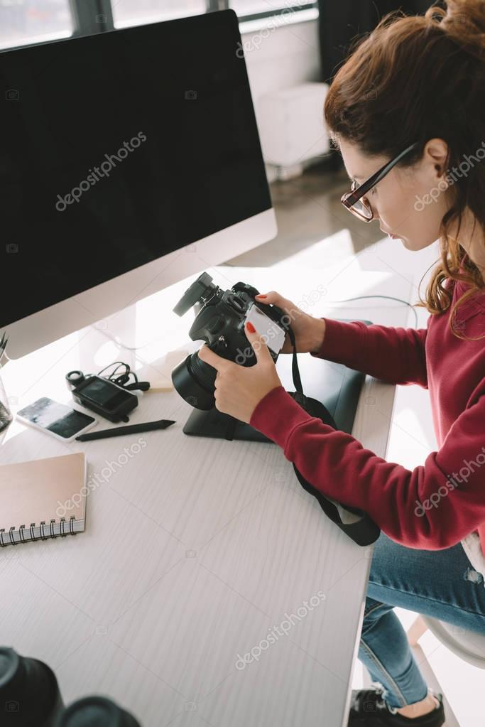 photographer with digital camera in office
