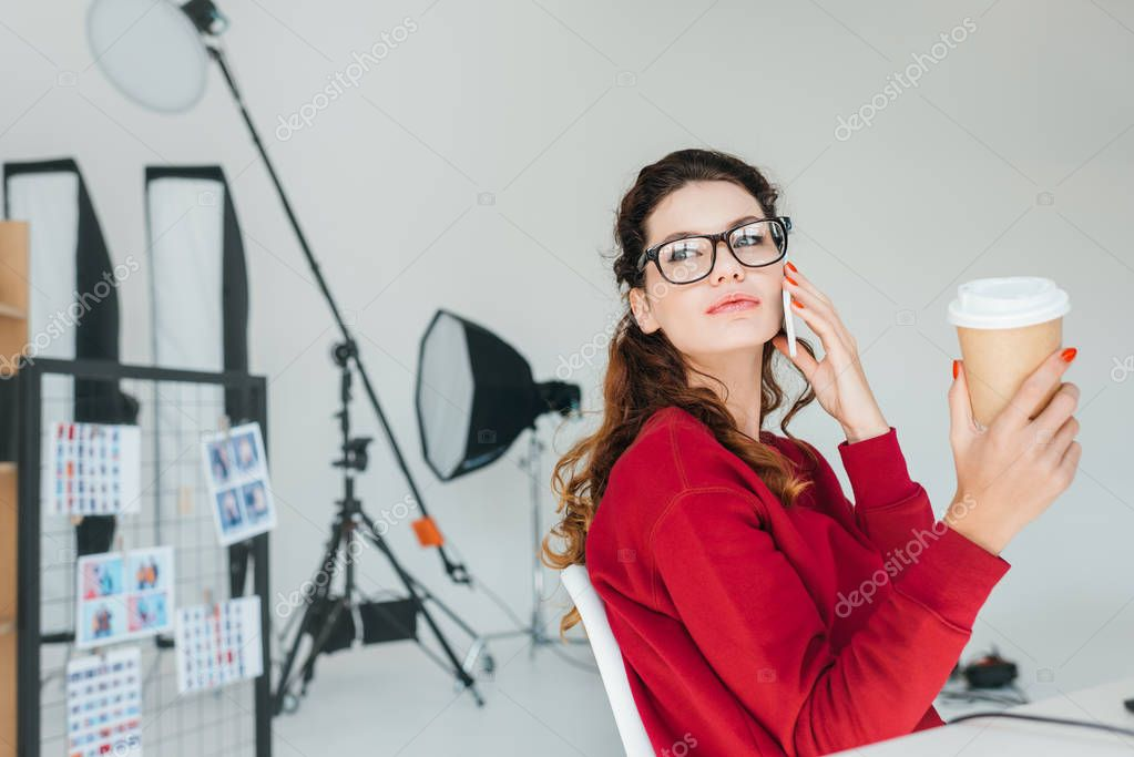 Female designer working with talking on smartphone in modern office stock vector