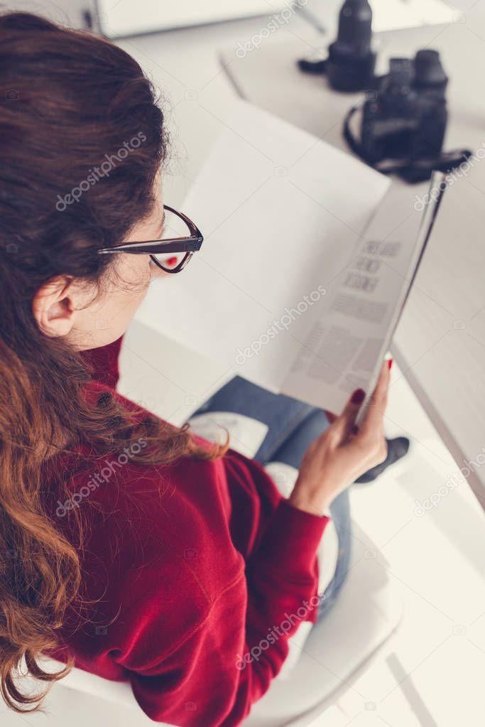 Back view of female designer reading magazine in modern office stock vector