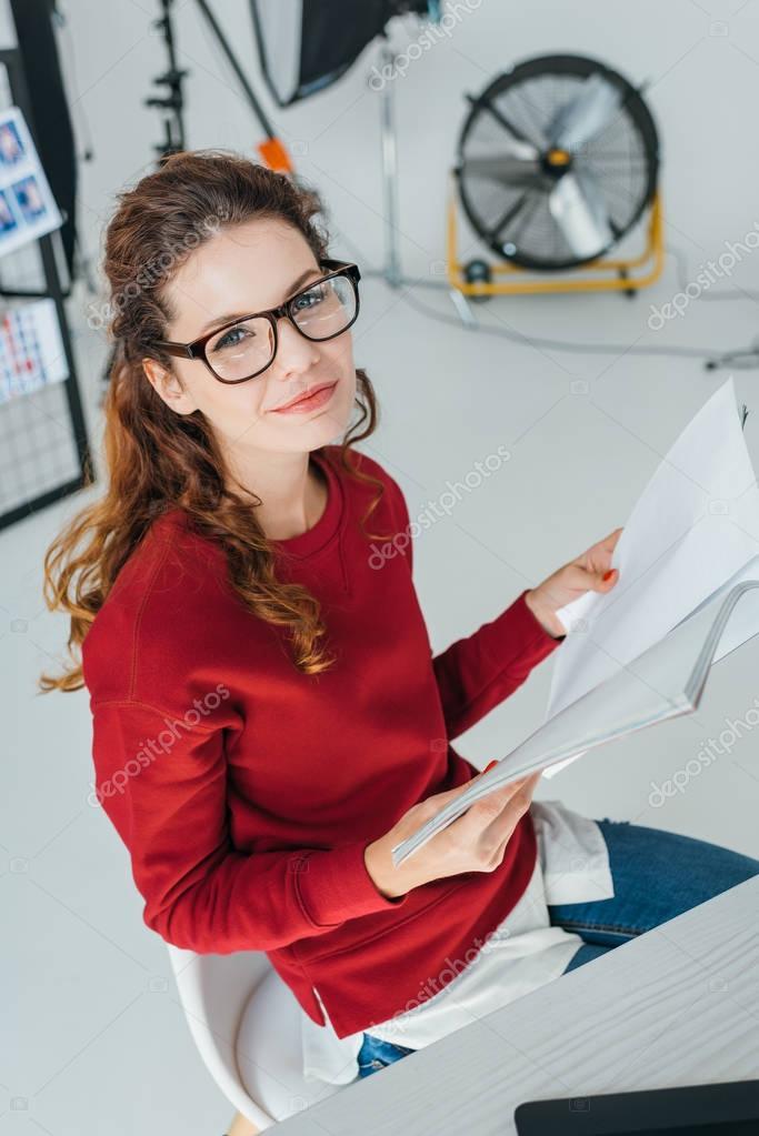 Beautiful female designer reading magazine in modern office stock vector