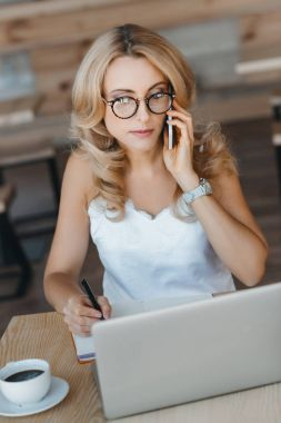 Businesswoman with laptop and smartphone