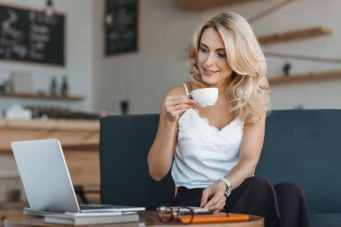 woman drinking coffee and using laptop