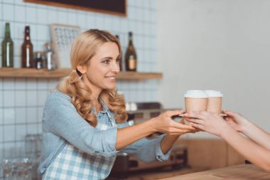 waitress holding disposable coffee cups