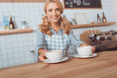 waitress holding cups of coffee