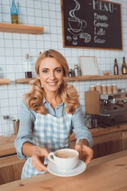 Waitress holding cup of coffee