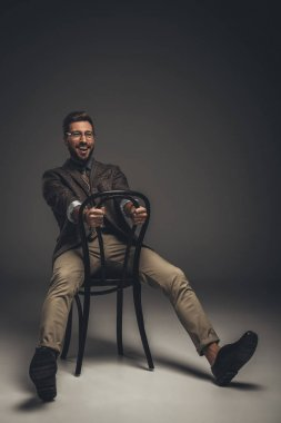man in suit sitting on chair backwards