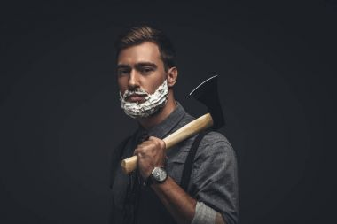 Man in shaving cream holding axe