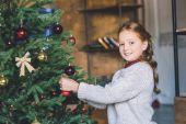 Fotografie girl decorating christmas tree
