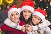 Mutter umarmt mit Kindern in Weihnachtsmützen