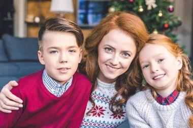 mother and kids embracing on christmas